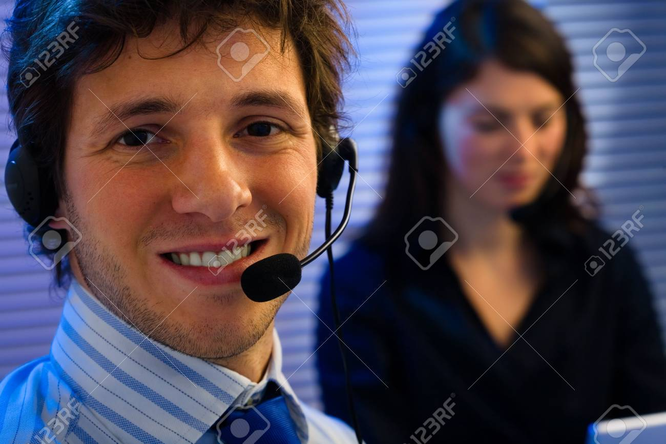 Male and female customer service representative working in office, smiling. Stock Photo - 2105430