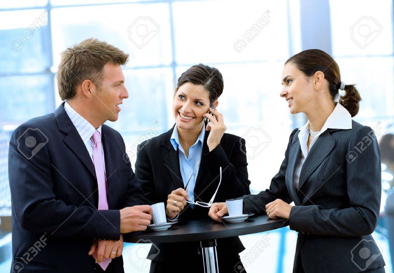 Young and happy business people standing around coffee table, drinking coffee and talking, smiling, indoor. Stock Photo - 3200009
