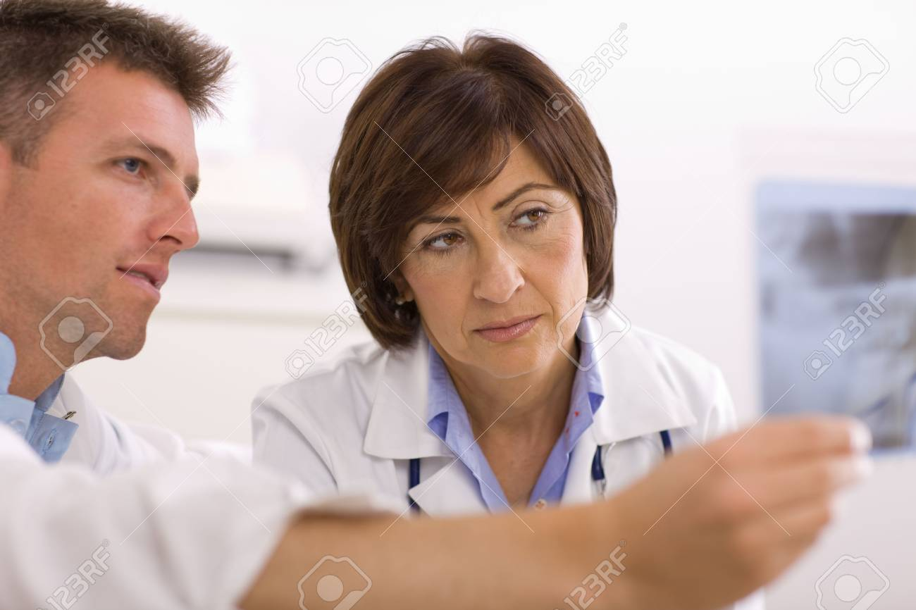 Doctors coworking looking at x-ray image at office. Stock Photo - 3868537