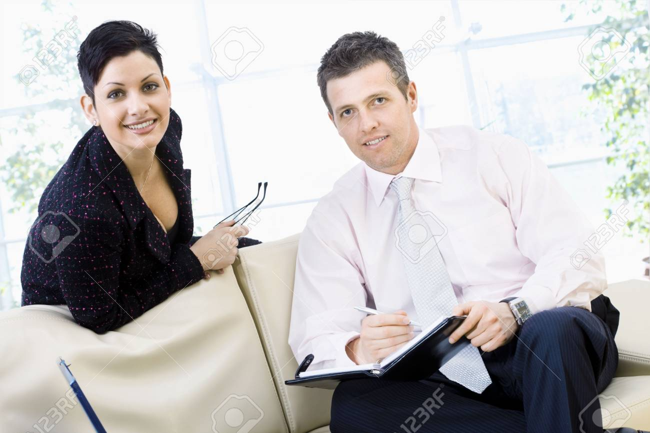 Happy businesspeople sitting of couch at office and  teamworking, they looking up to camera and smiling. Stock Photo - 3884372