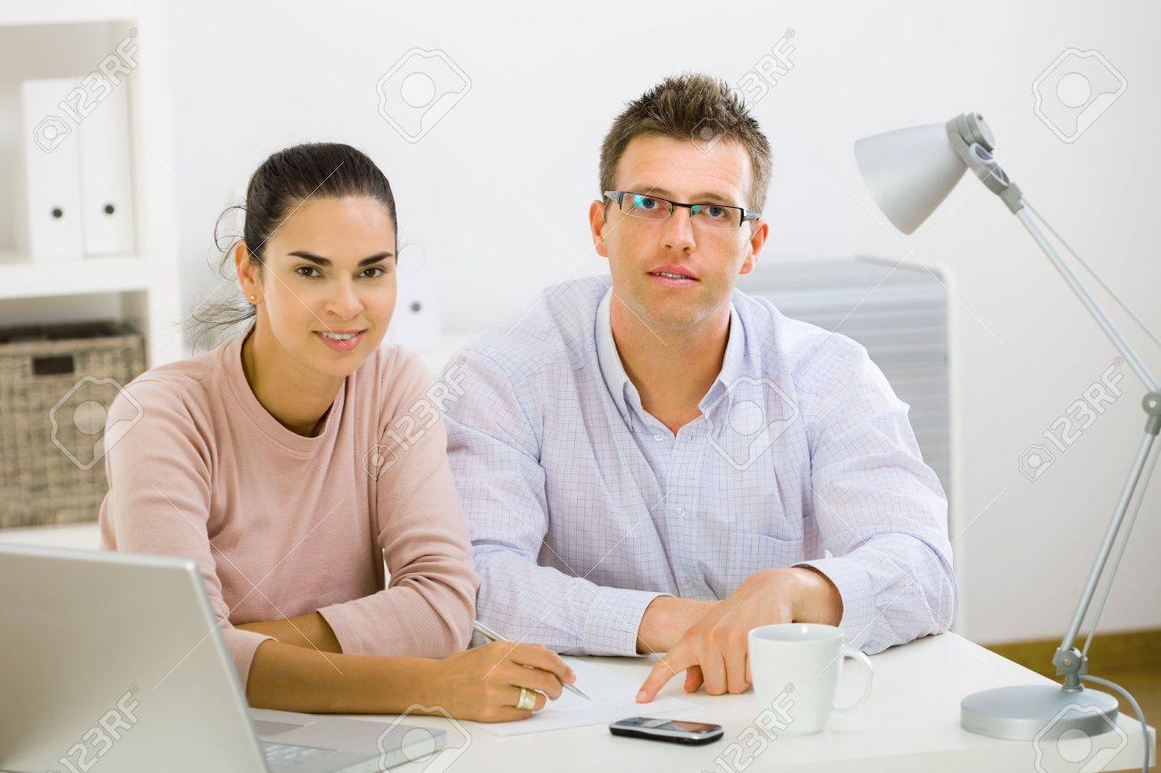 Couple working on laptop computer at home office, happy, smiling. Stock Photo - 3884374