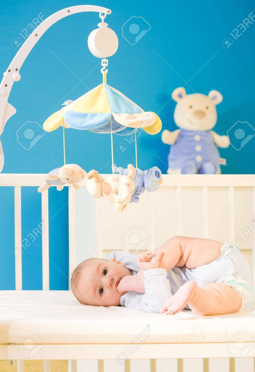 Infant baby resting and playing in his little baby bed at nursery. Toys are officially property released. Stock Photo - 3889277