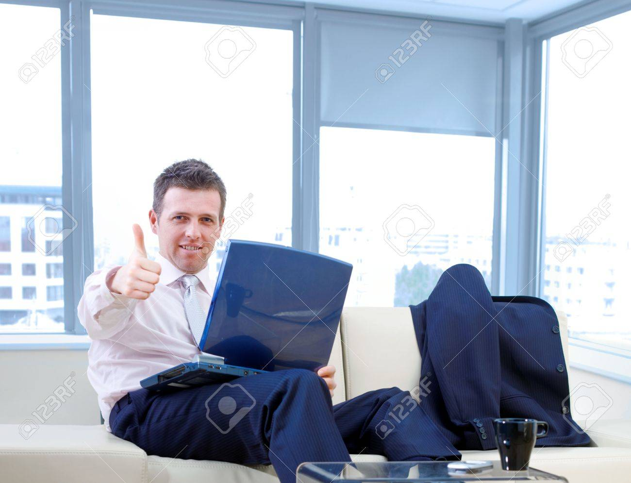Happy successful businessman sitting on couch at office, working on laptop compute, smiling and showing okay hand sign. Stock Photo - 3916138