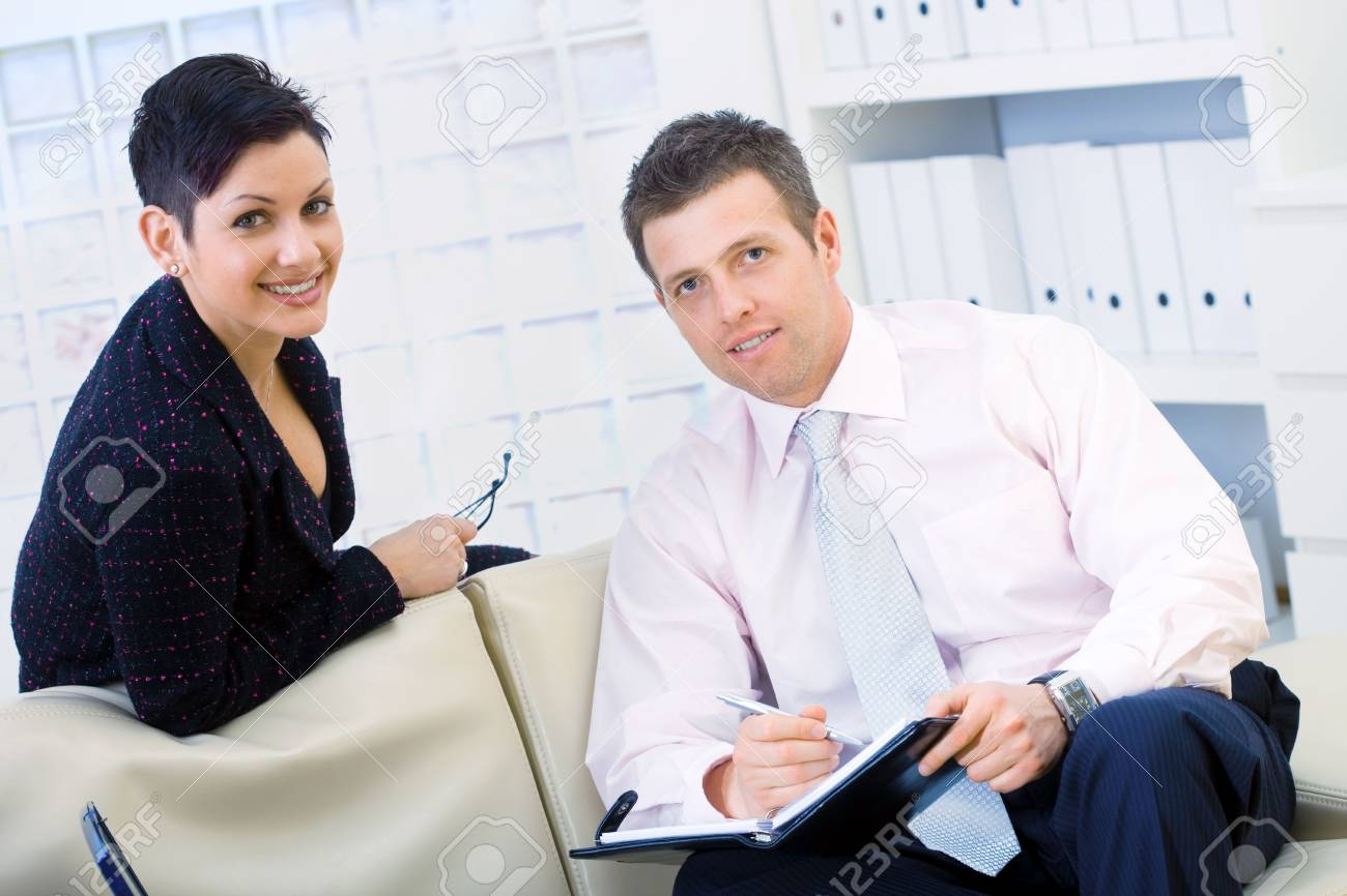 Smiling coworkers, businessman and businesswoman sitting on sofe and working together at office, doing paperwork. Stock Photo - 3916182