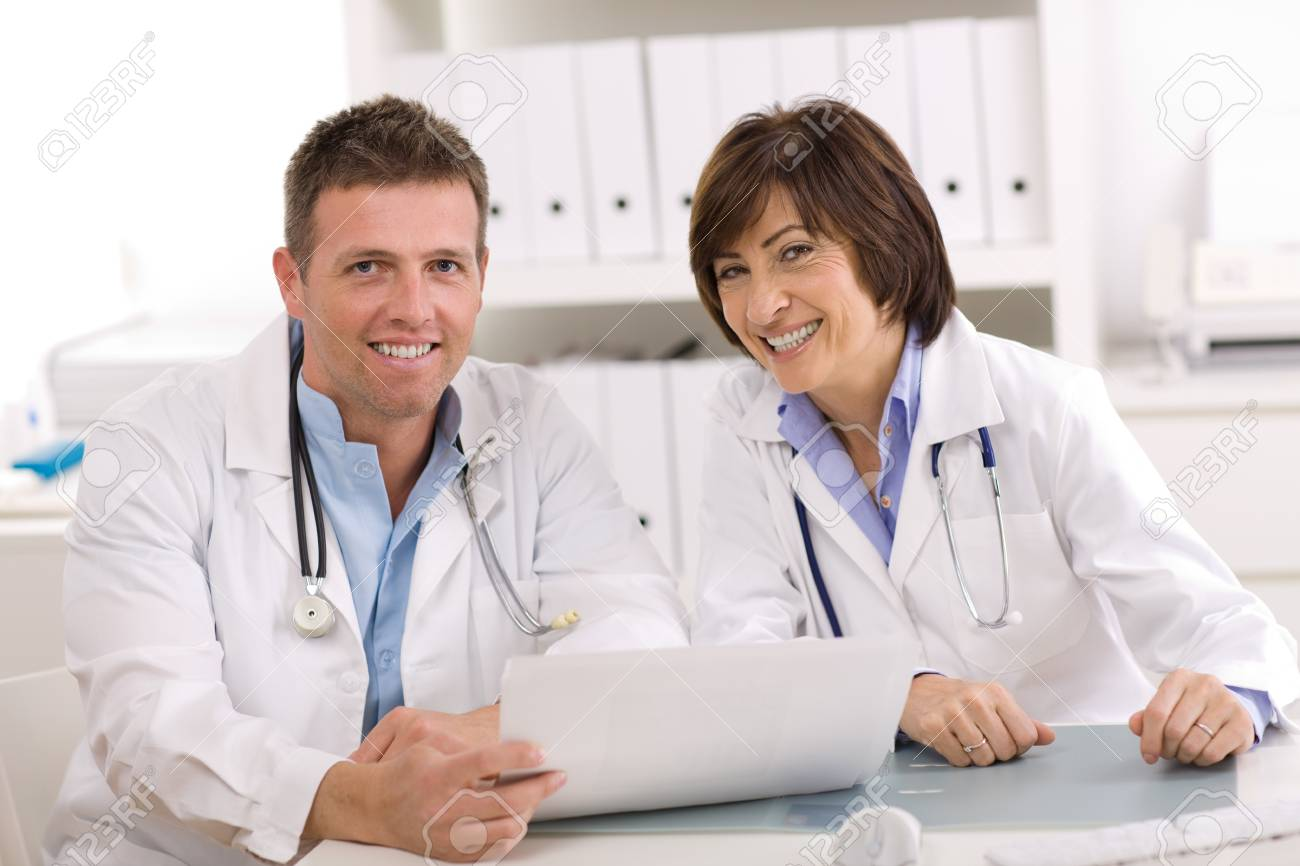 Medical team of male and female doctors sitting at desk. Stock Photo - 3979656