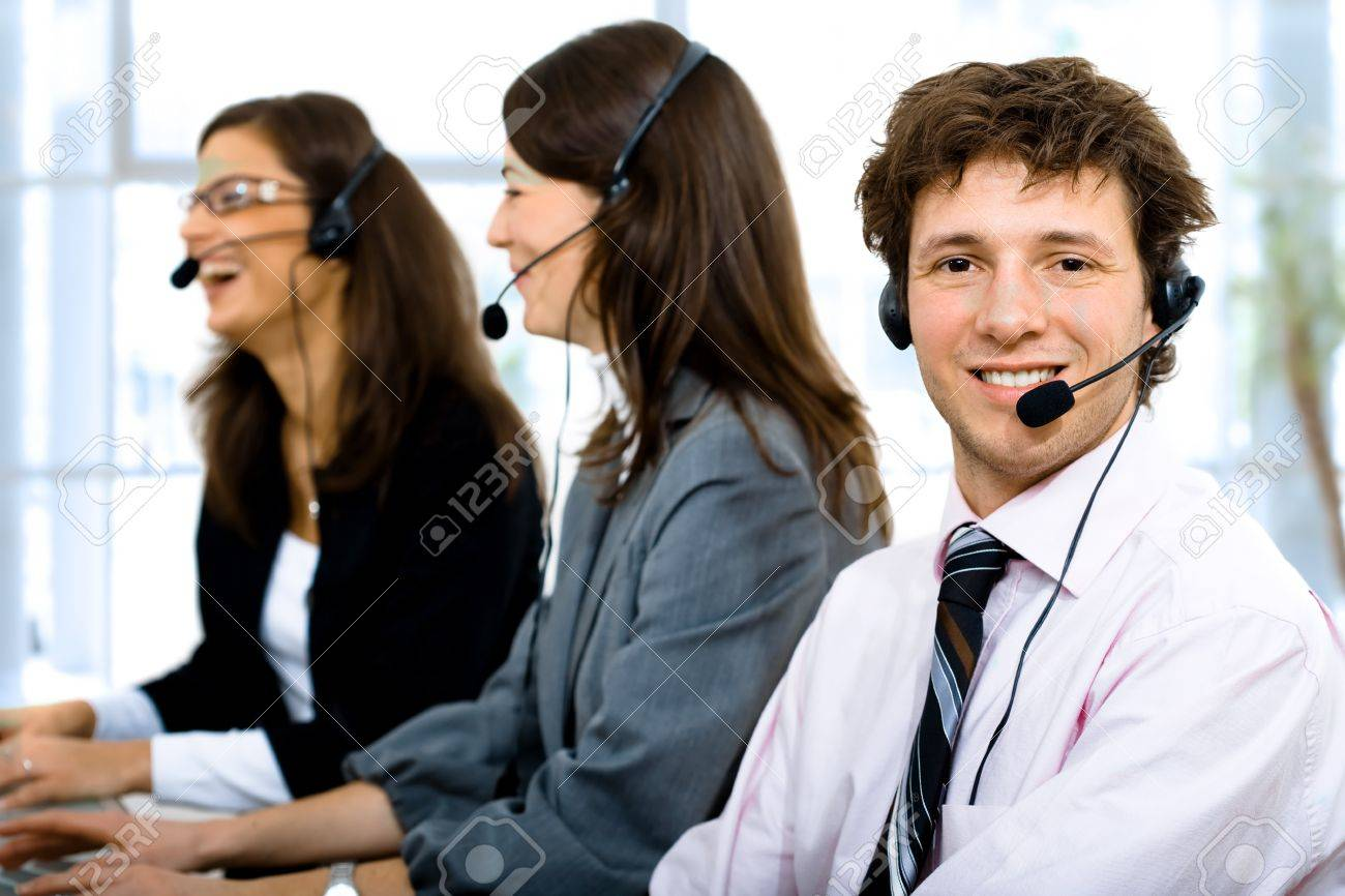 customer service team working in headsets smiling man in front customer service team working in headsets smiling man in front stock photo