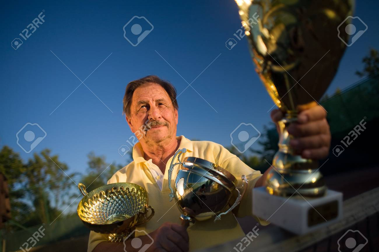 Active senior man in his 70s is posing on the tennis court with cups in hands. Outdoor, sunlight. Stock Photo - 4100530