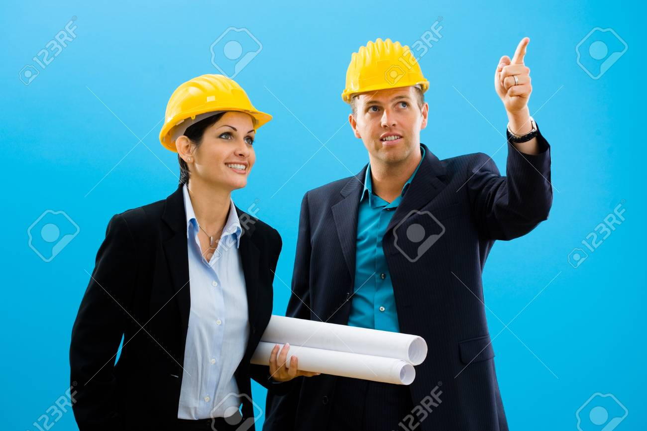 Young architects in yellow hardhat against blue background. Stock Photo - 4100529