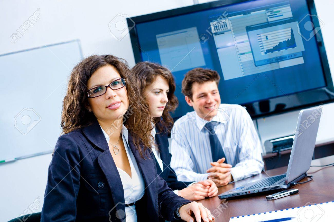 Small team of young businesspeople working together at meeting room at office. Huge plasma TV screen in background. Stock Photo - 4107038