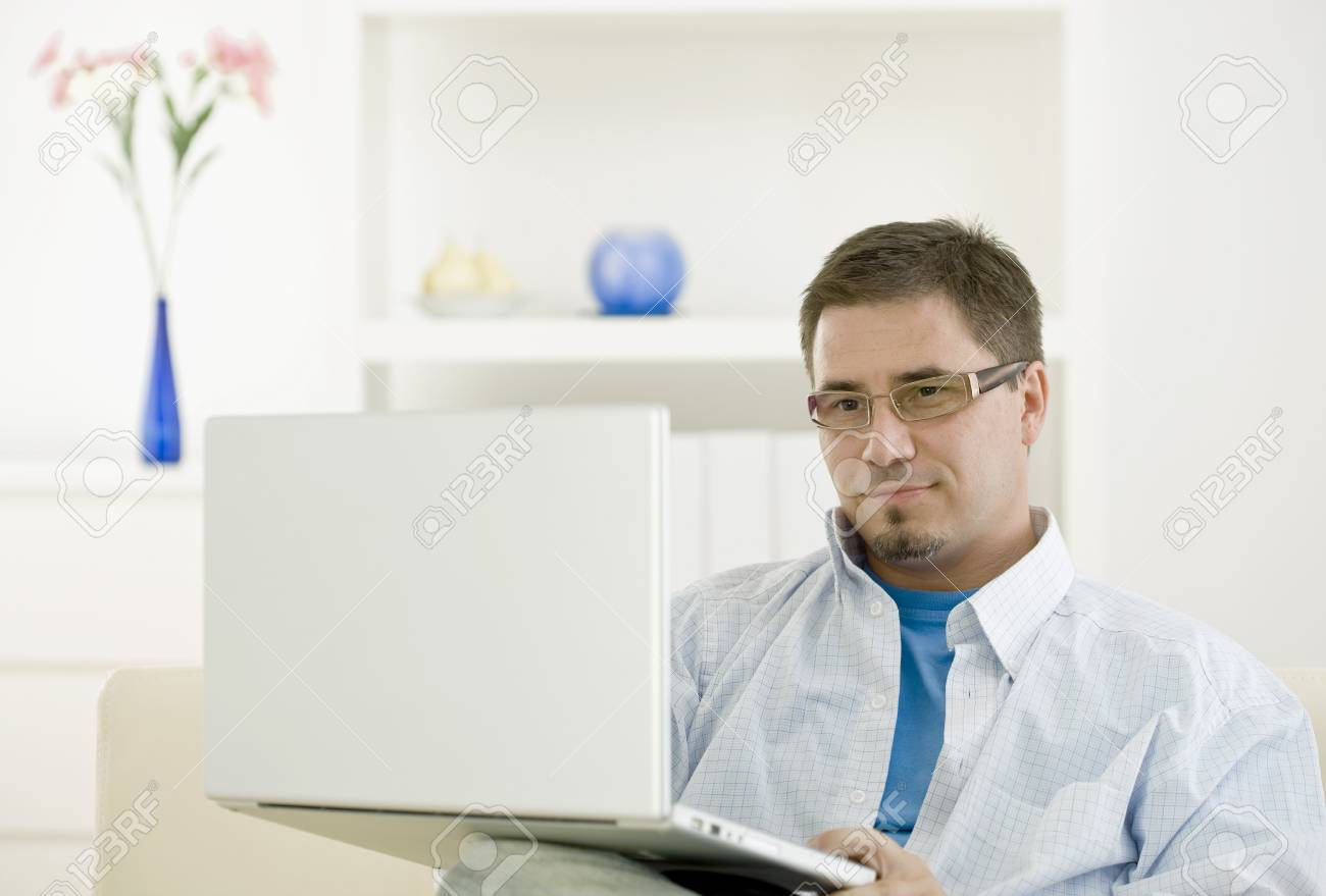 Happy casual man teleworking using laptop computer at home. Stock Photo - 4121286
