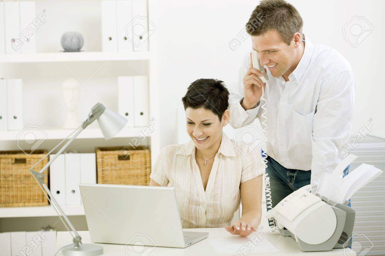 Happy couple working at home using laptop computer, smiling. Stock Photo - 4121299