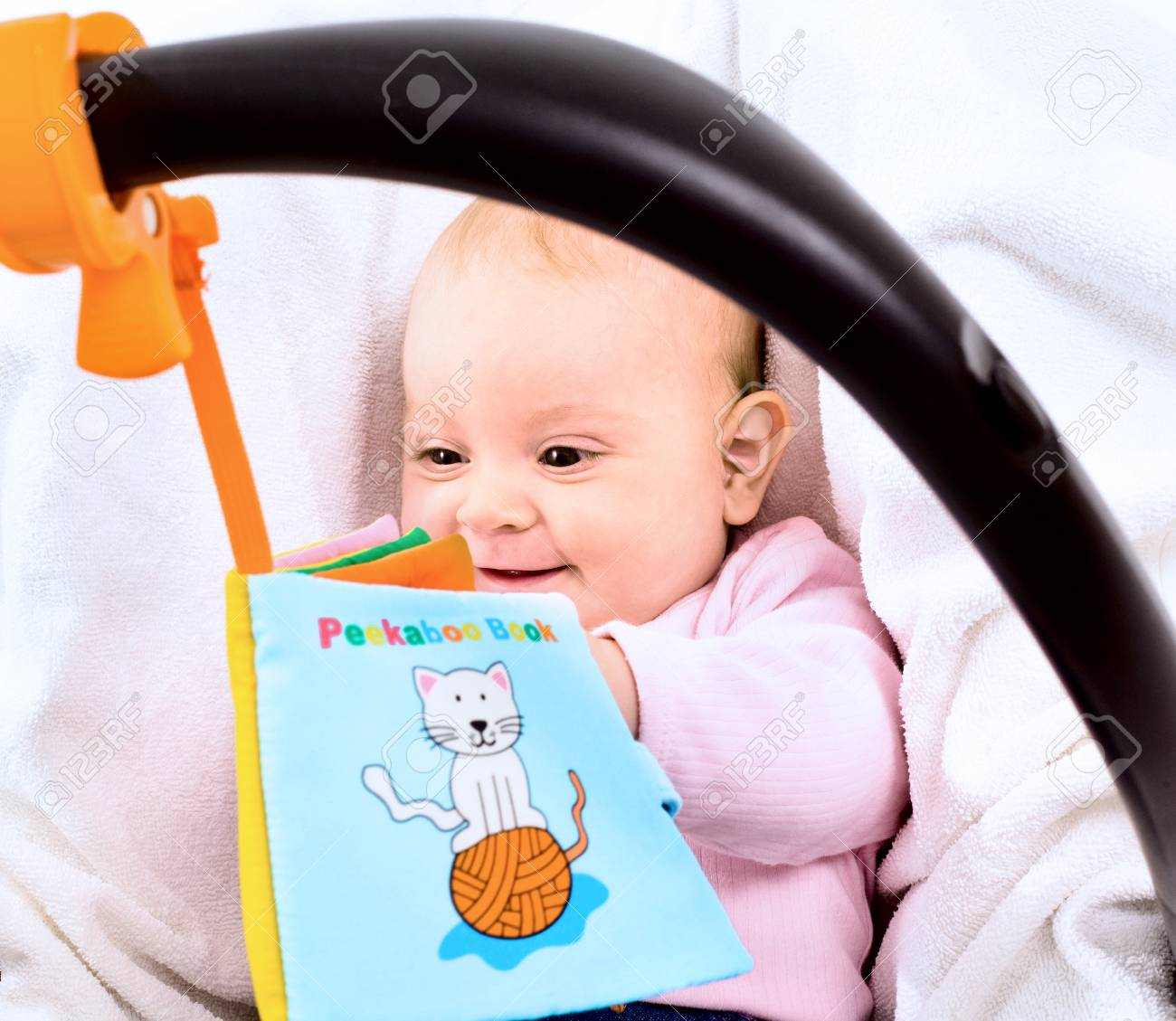 Baby playing with story book sitting in baby carrier. Stock Photo - 4121315
