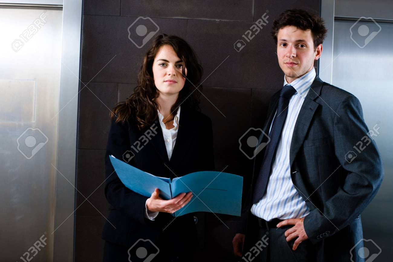 Businesswoman and businessman reviewing documents at office lobby in front of elevator. Dark background. Stock Photo - 4130618
