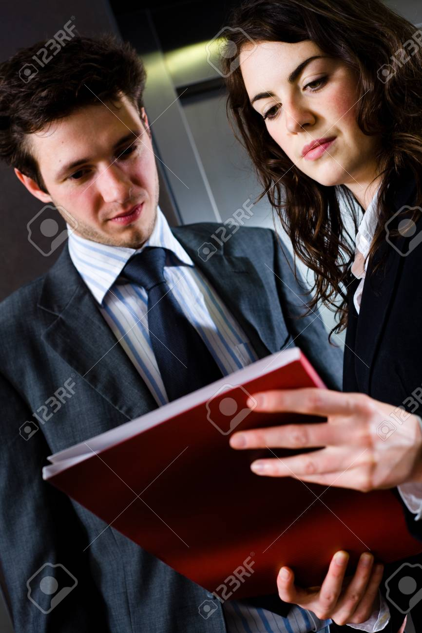 Young businesspeople working together at office corridor, looking at red document folder, reading reports. Stock Photo - 4130603