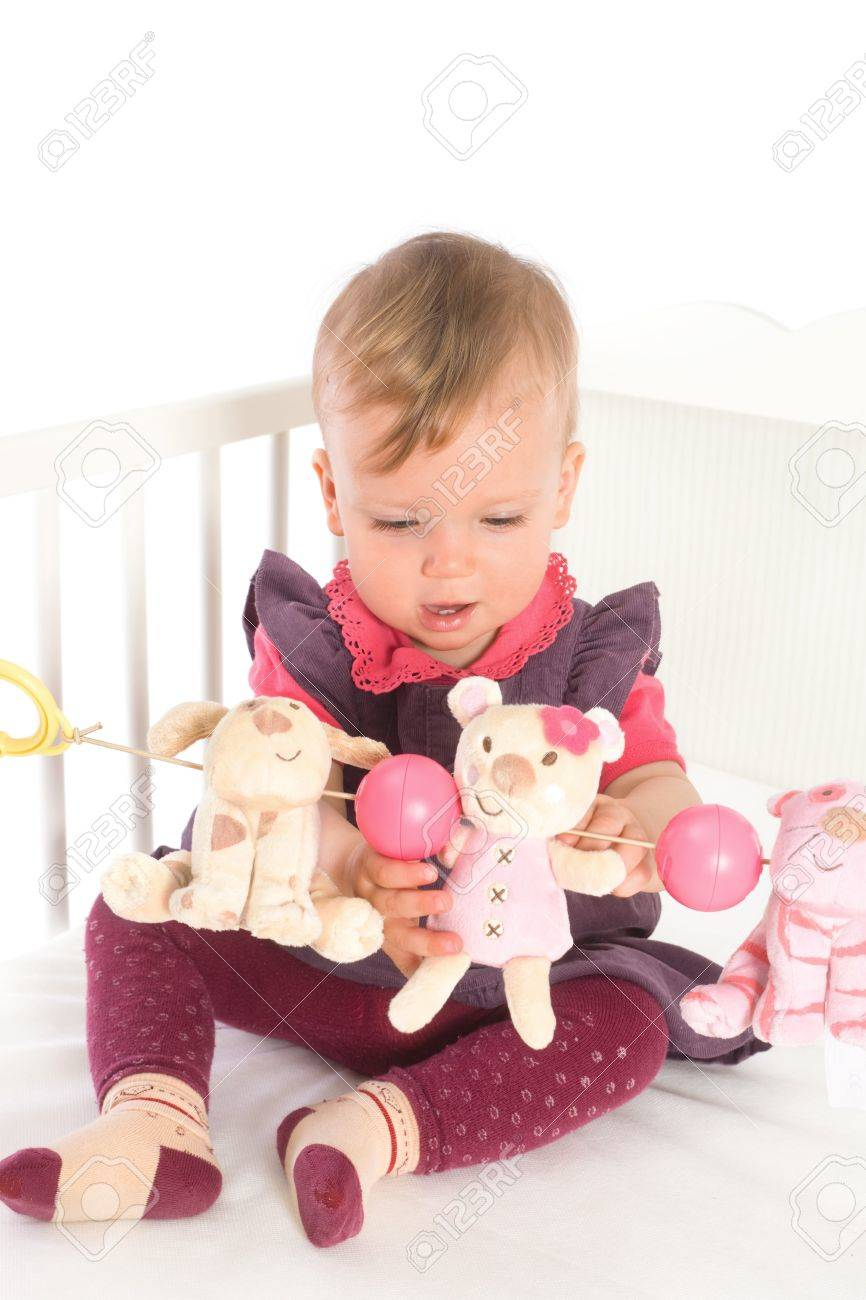 Cute Baby Girl 1 Year Old Sitting On Crib Holding Soft Toys