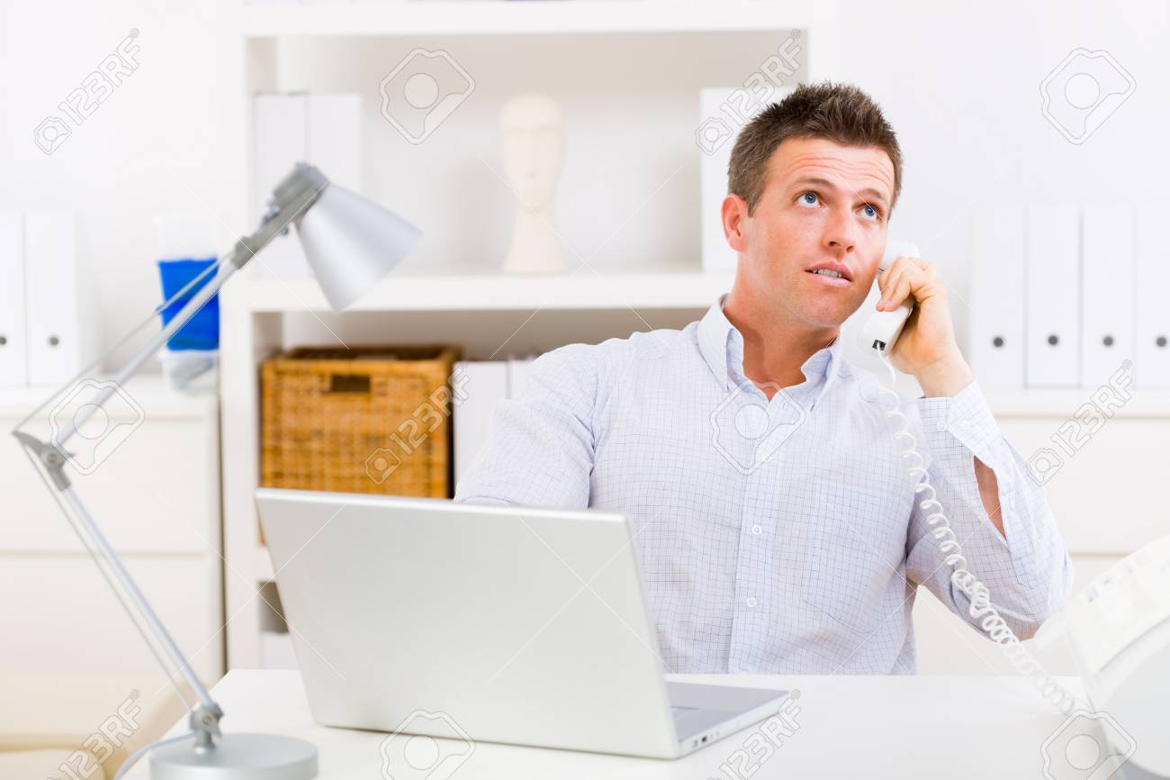 Business man working on computer at home calling on phone. Stock Photo - 4161161