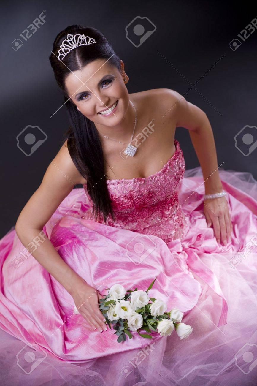 Feliz Joven Novia Posando En Un Traje De Novia De Color Rosa, La ...