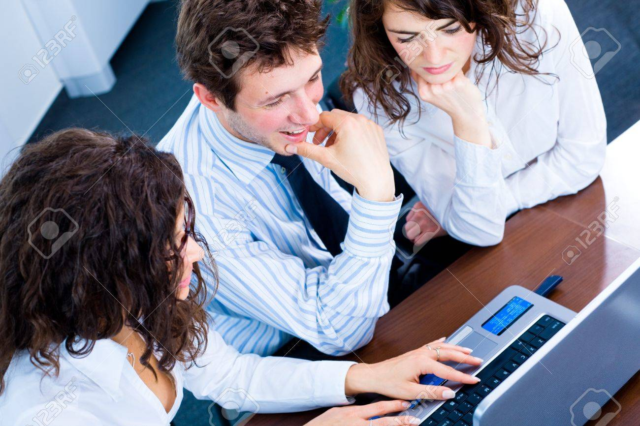 Happy team of young business people sitting in meeting room, working together on laptop computer, smiling. Overhead view. Stock Photo - 4193377