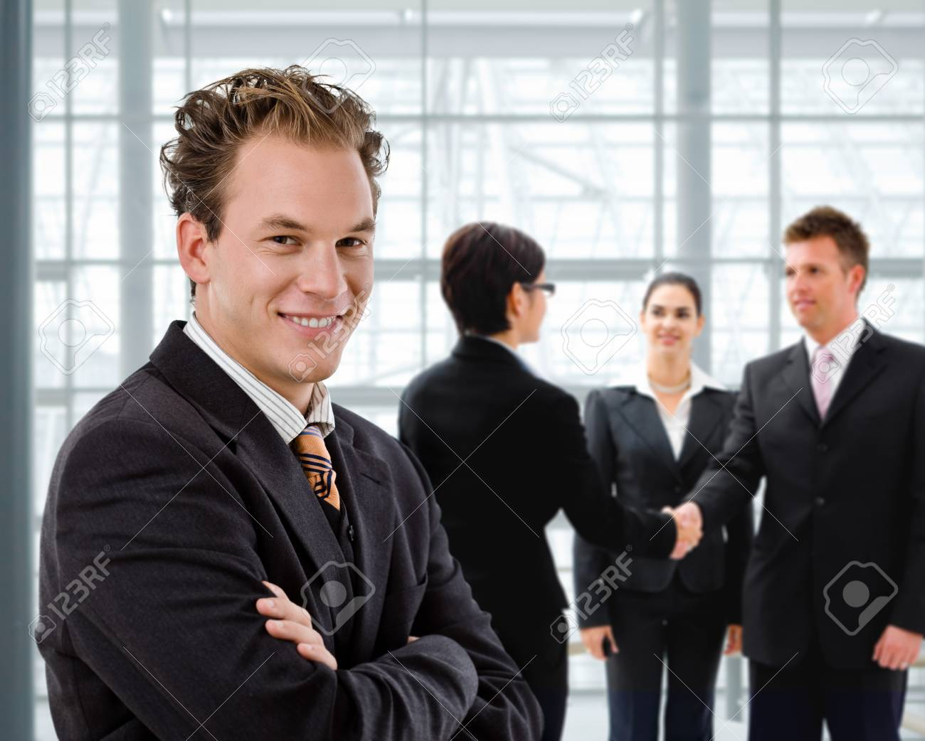 Team of business people, businessman in front, handsake in background. Stock Photo - 4209137