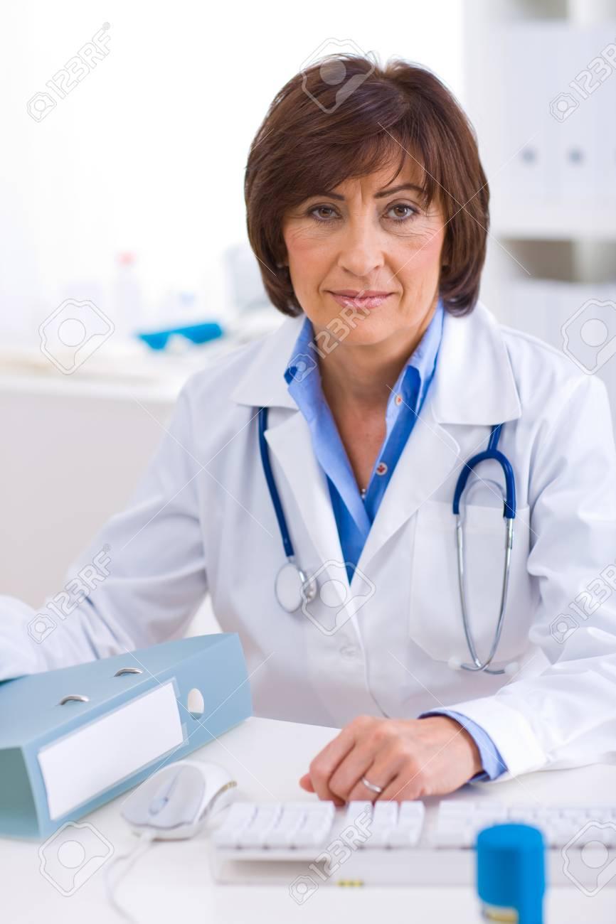 Senior female doctor sitting at desk working at offiice. Stock Photo - 4209102