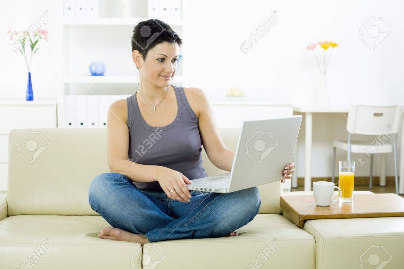 Young woman sitting on sofa at home working on laptop computer. Stock Photo - 4241375