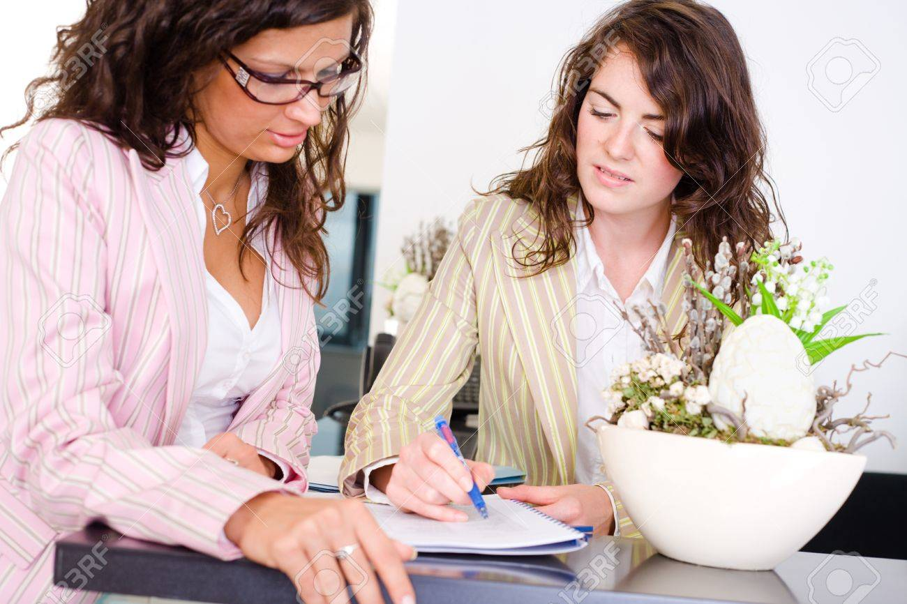 Casual businesswomen working together in team at office reception, looking at documents, talking. Stock Photo - 4244947