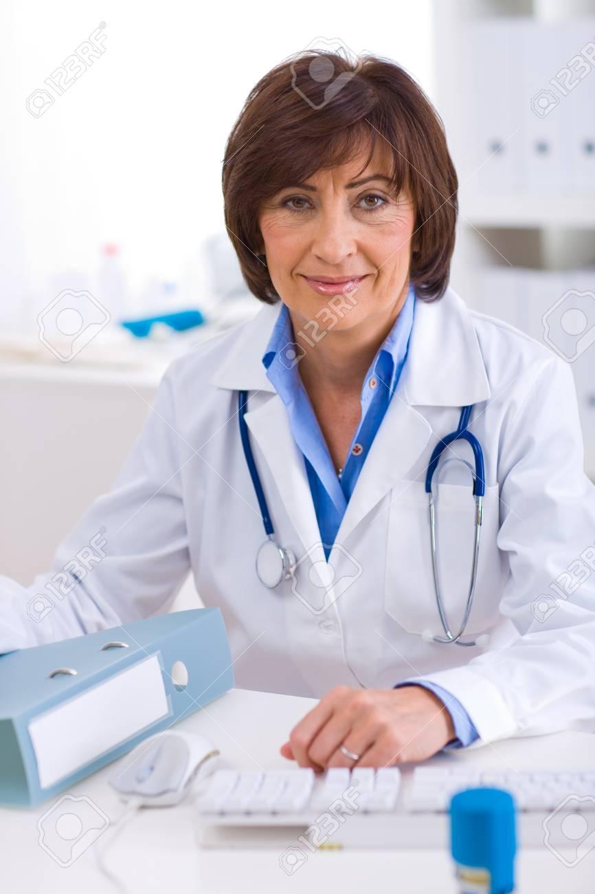 Senior female doctor sitting at desk working at offiice. Stock Photo - 4245069