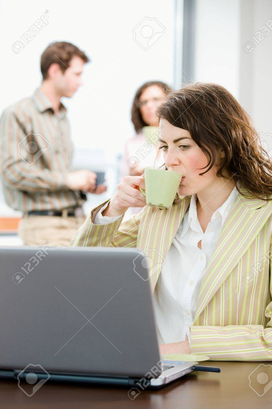 Team of young successful office workers talking and drinking coffee at meeting room, businesswoman working on laptop computer in front. Stock Photo - 4366459