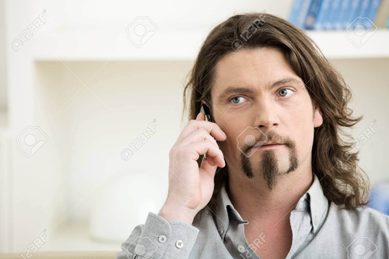 Casual man wearing grey shirt talking on mobile phone. Stock Photo - 4366489