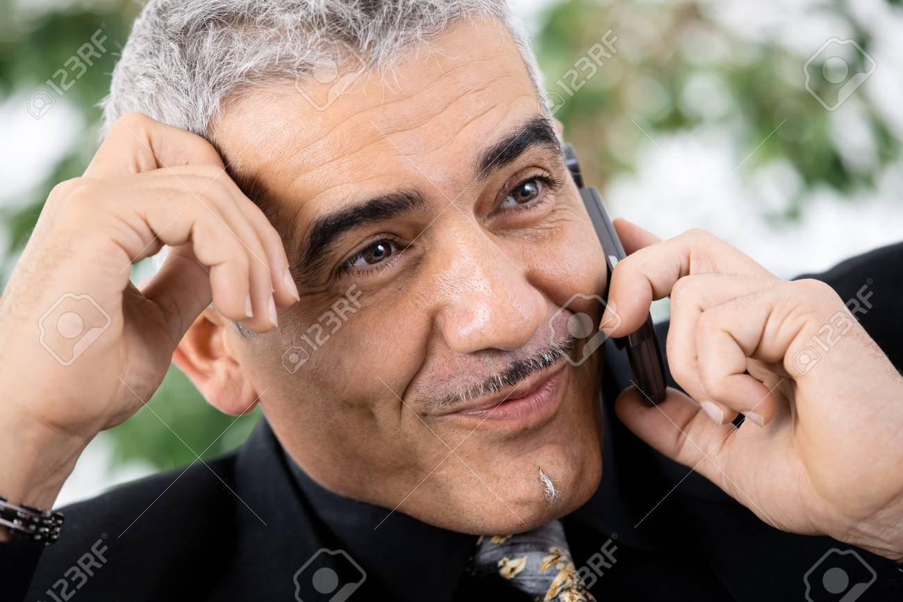 Gray haired mature businessman calling on mobile phone, smiling. Stock Photo - 4403230