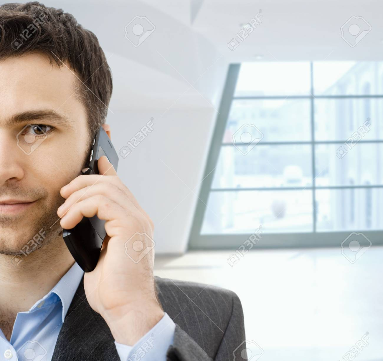 Closeup portrait of casual businessman talking on mobile phone, standing in office lobby. Stock Photo - 4560105