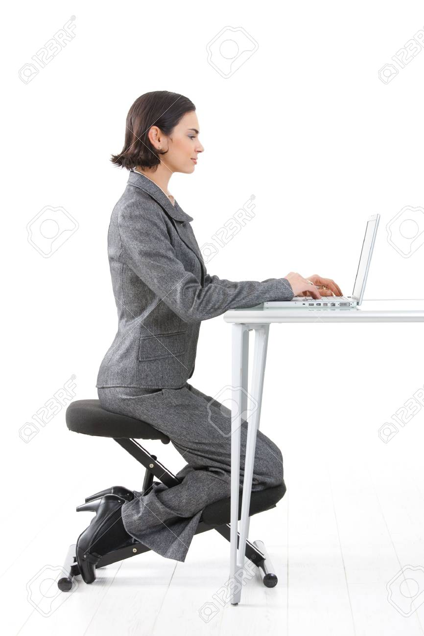 Young happy businesswoman working on kneeling chair, smiling, isolated on white. Stock Photo - 4559832