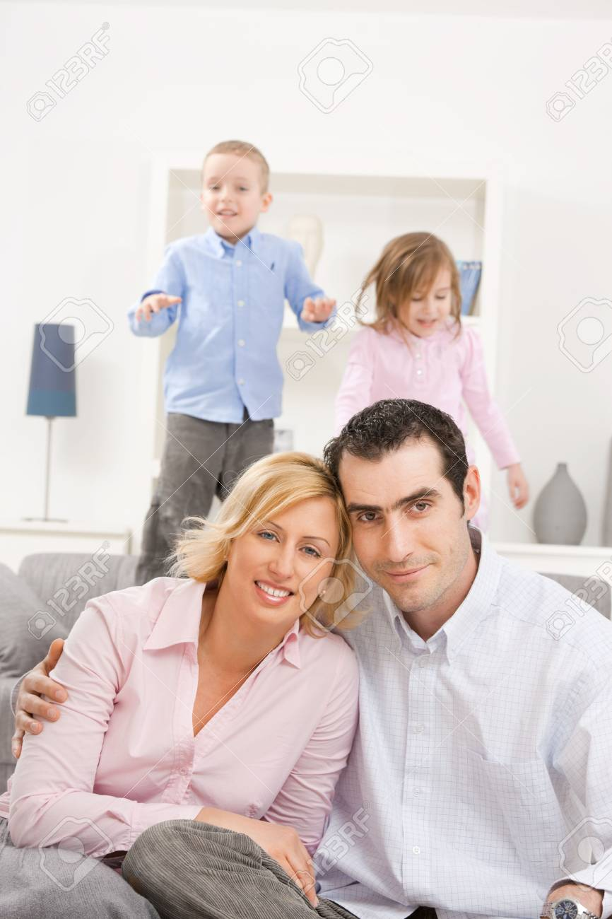 Happy couple sitting at floor at home, embracing. Two children jumping on couch in background. Stock Photo - 5024729