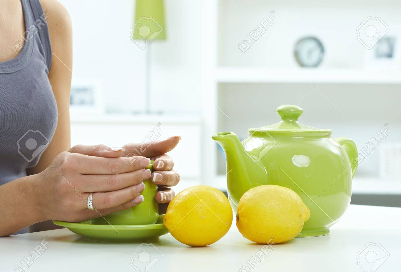 Female hands holding tea cup on table, along with green jug and lemones. Stock Photo - 5041663