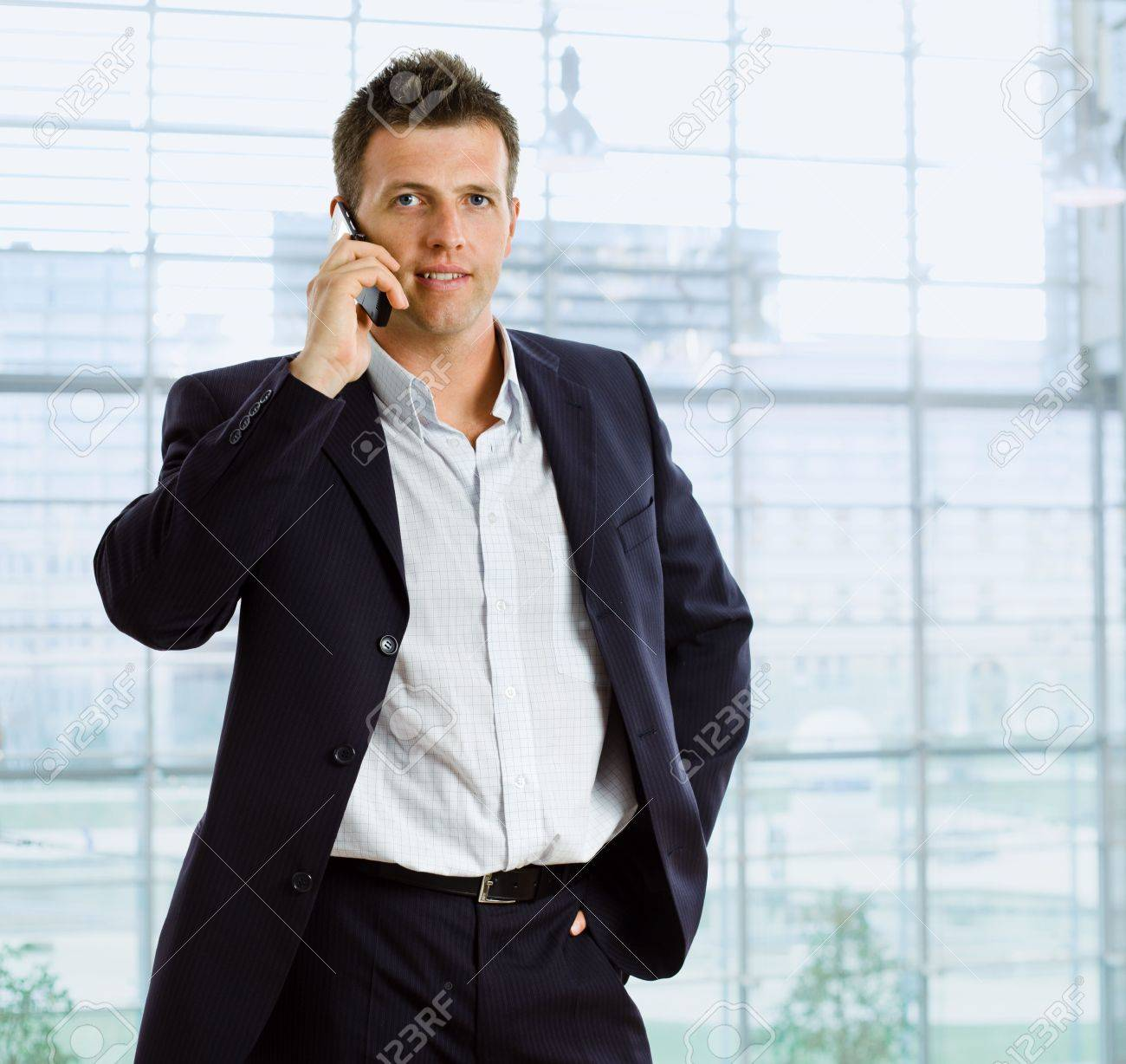 Businessman talking on mobile phone in front of office window. Stock Photo - 5035342