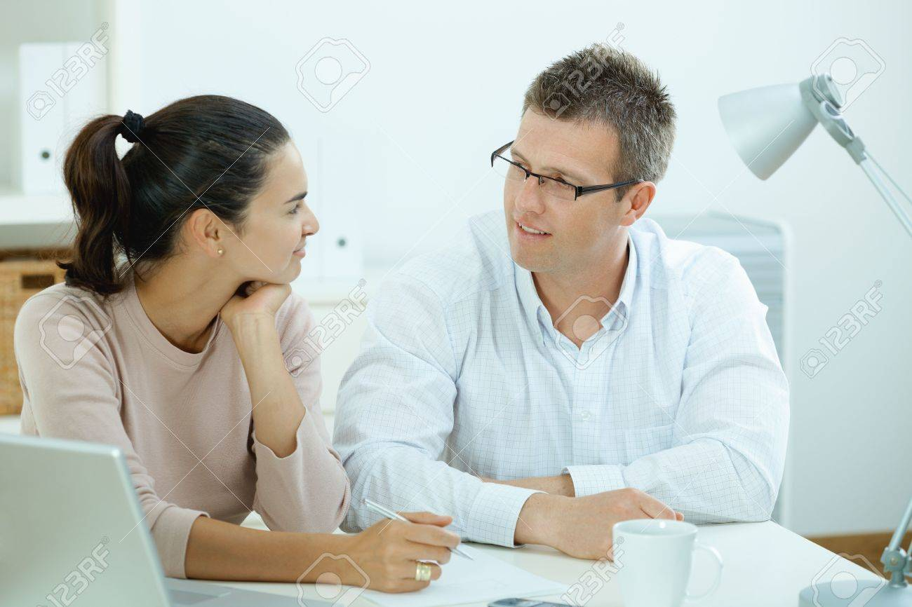 Happy young casual couple sitting  at desk working together at home office, smiling. Stock Photo - 5101978