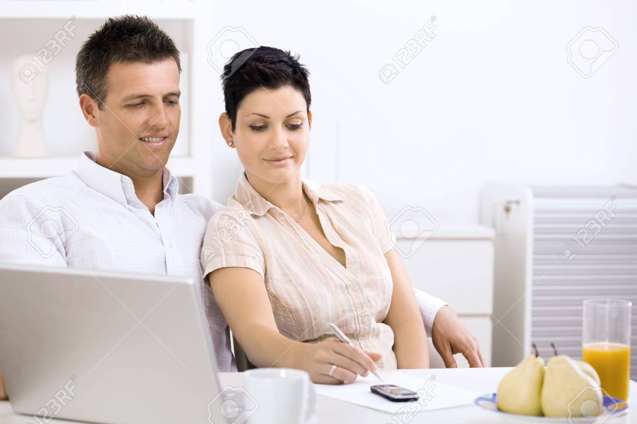 Couple working at home office, planning on paper. Stock Photo - 5101640