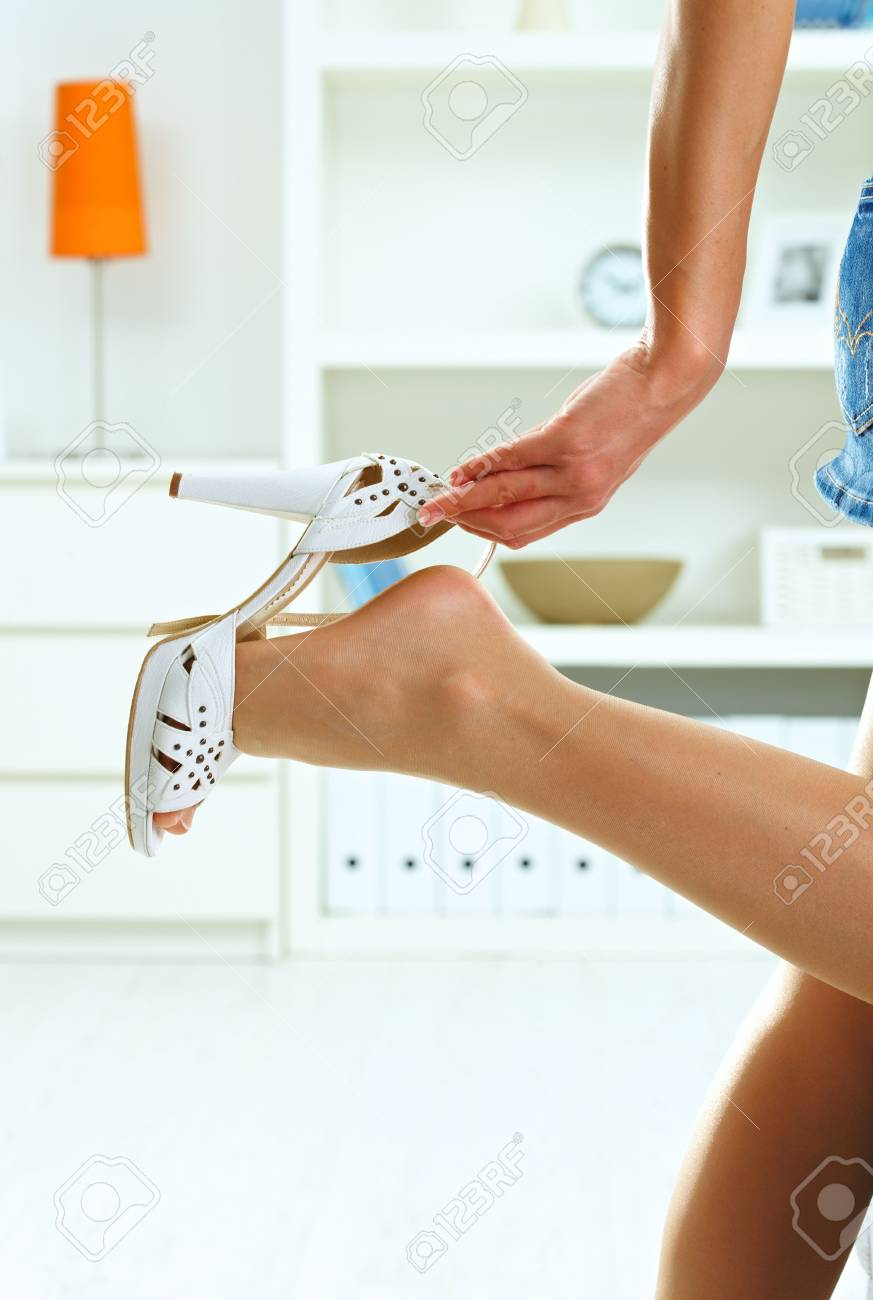 Closeup photo of female leg and hand. Woman taking off her high heel shoe. Stock Photo - 5732496