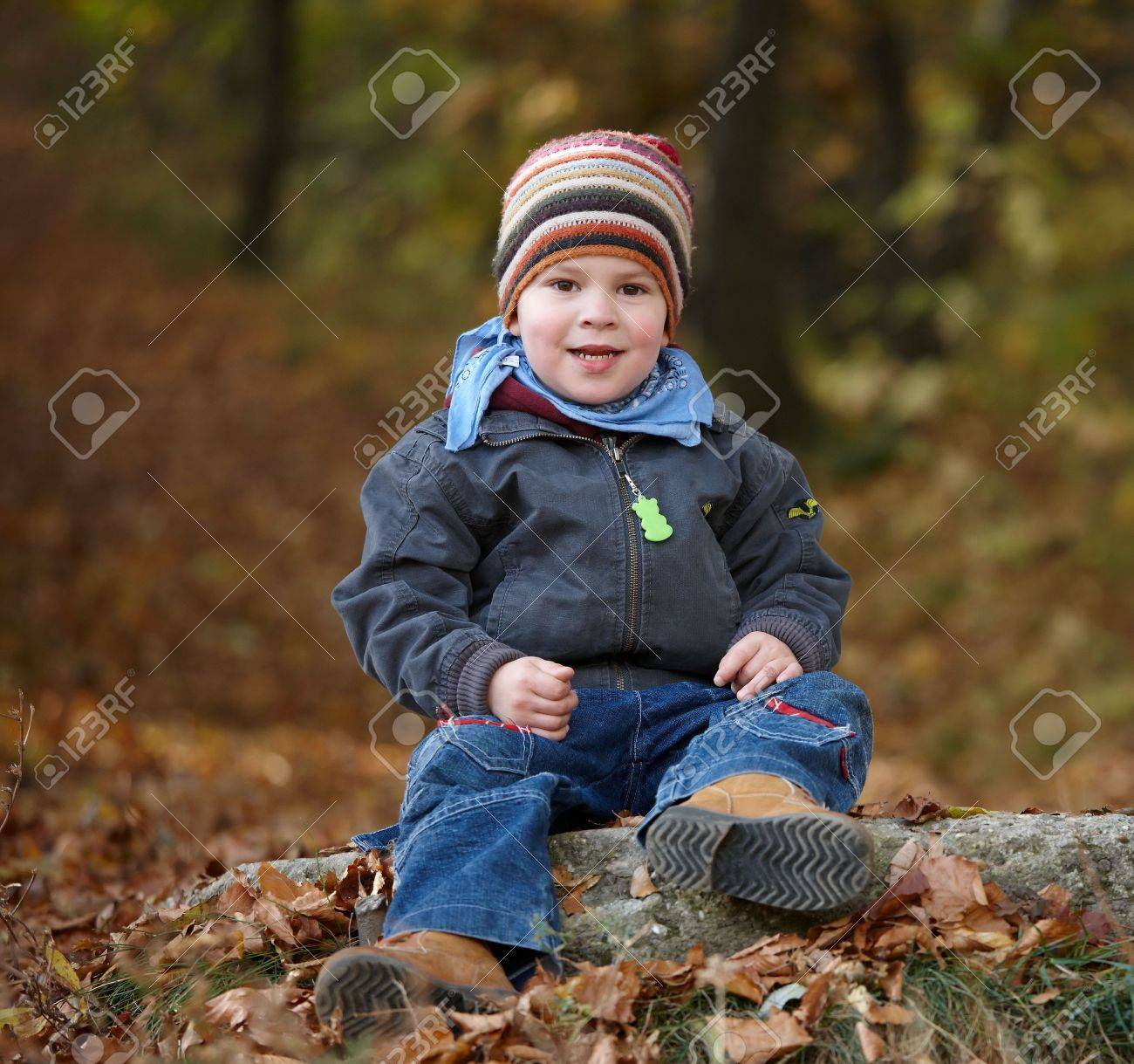 Happy kid in coat and cap playing outdoor in autumn forest, smiling. Stock Photo - 5724719