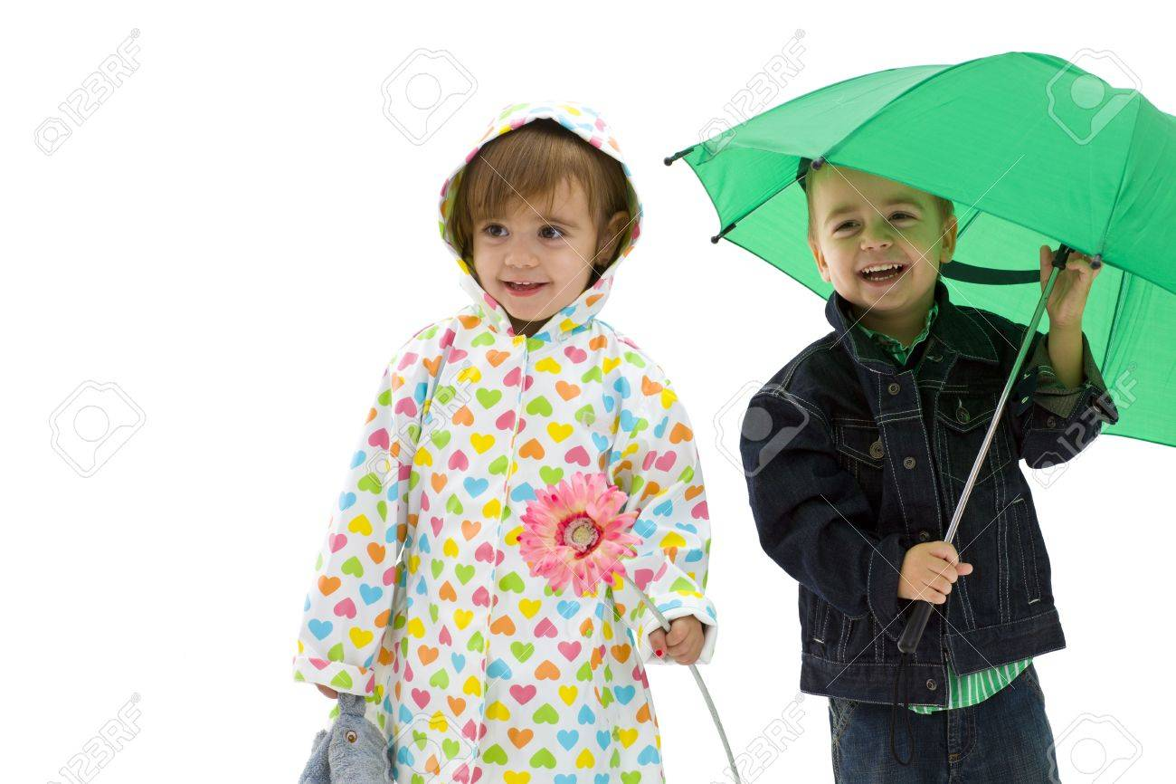 Happy laughing children. Boy holding a green umbrella. Girl wearing raincoat and holding flower. Isolated on white background. Stock Photo - 5724671