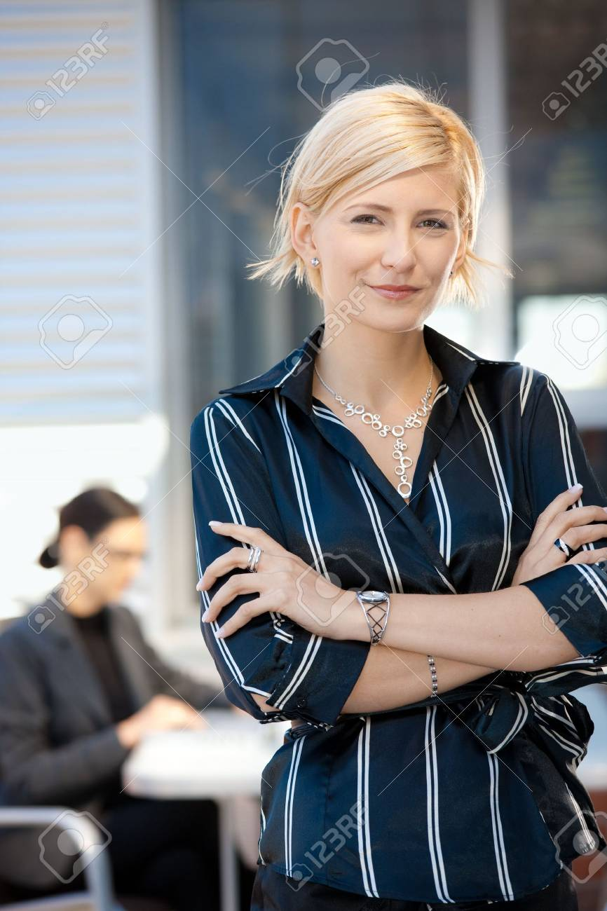 Portrait of attractive young businesswoman standing arms crossed, smiling. Stock Photo - 5741843