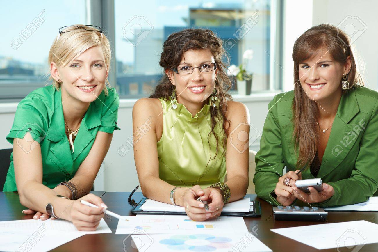 Group of attractive businesswomen sitting at meeting room, discussing financial charts on table, smiling. Stock Photo - 5742721