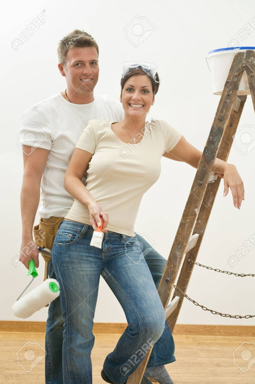 Young copule posing with ladder, holding paint roller and brush, smiling. Stock Photo - 5747171