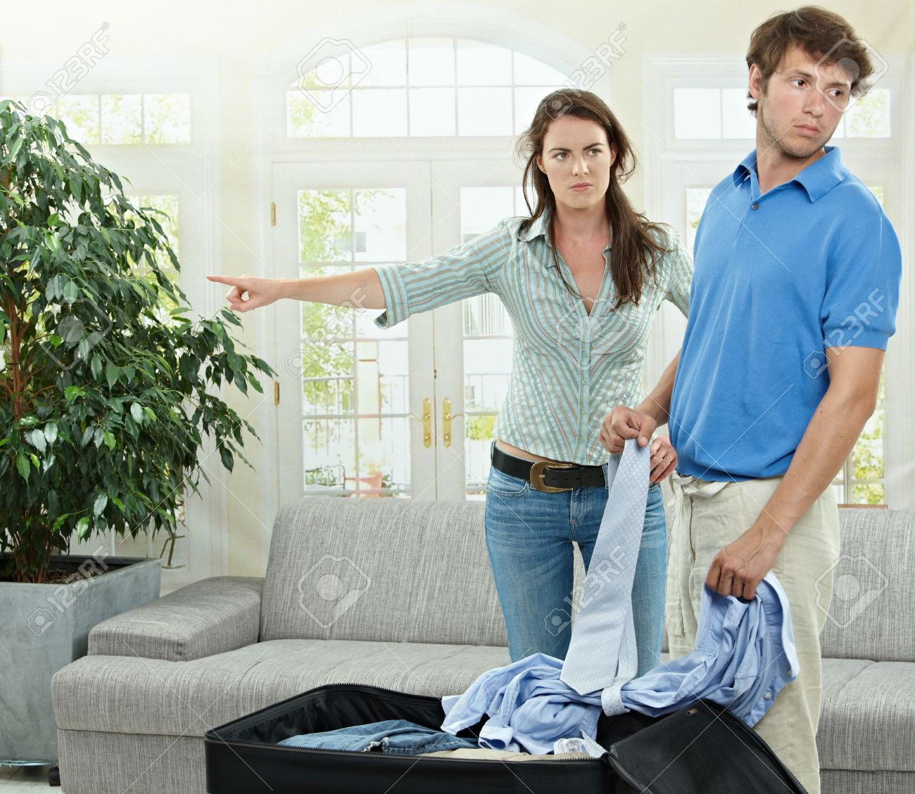 Unhappy couple breaking. Angry woman pointing out, man packing his clothes into suitcase. Stock Photo - 5754779