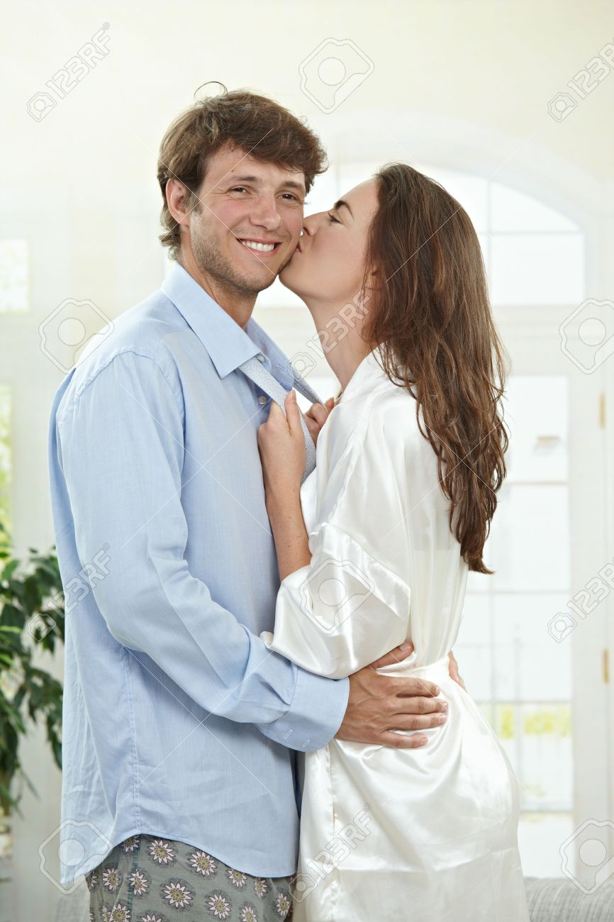 happy couple embracing and kissing at home in the morning stock