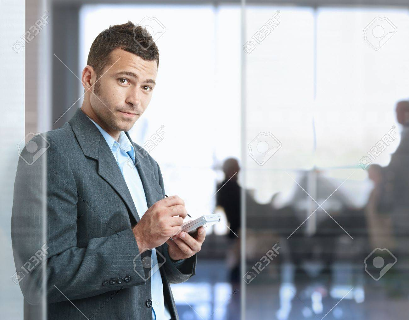 Serious businessman standing in office lobby , using smart phone, looking at camera. Stock Photo - 5758767