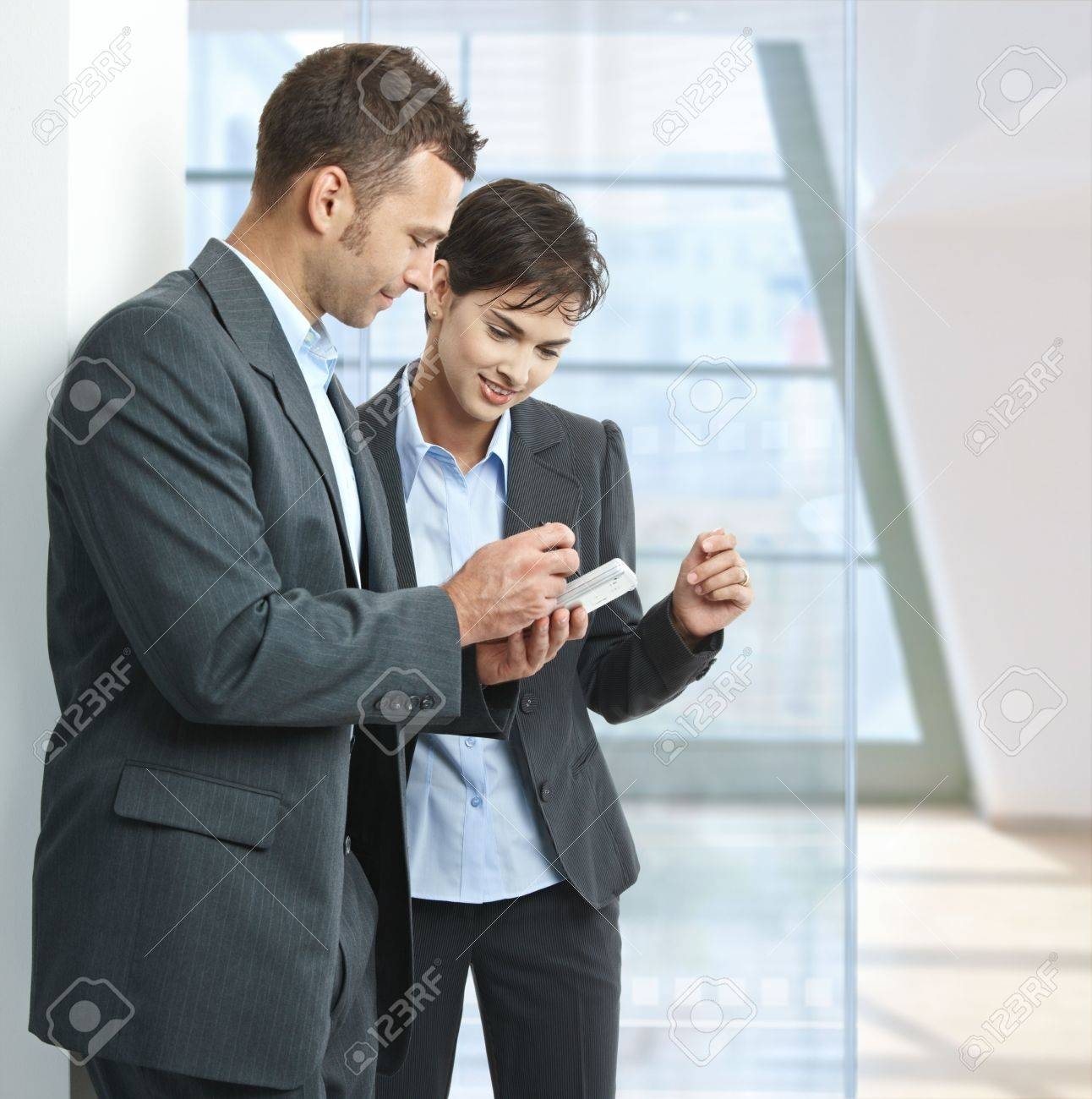 two businesspeople standing in office lobby looking at smart stock photo two businesspeople standing in office lobby looking at smart mobile phone smiling