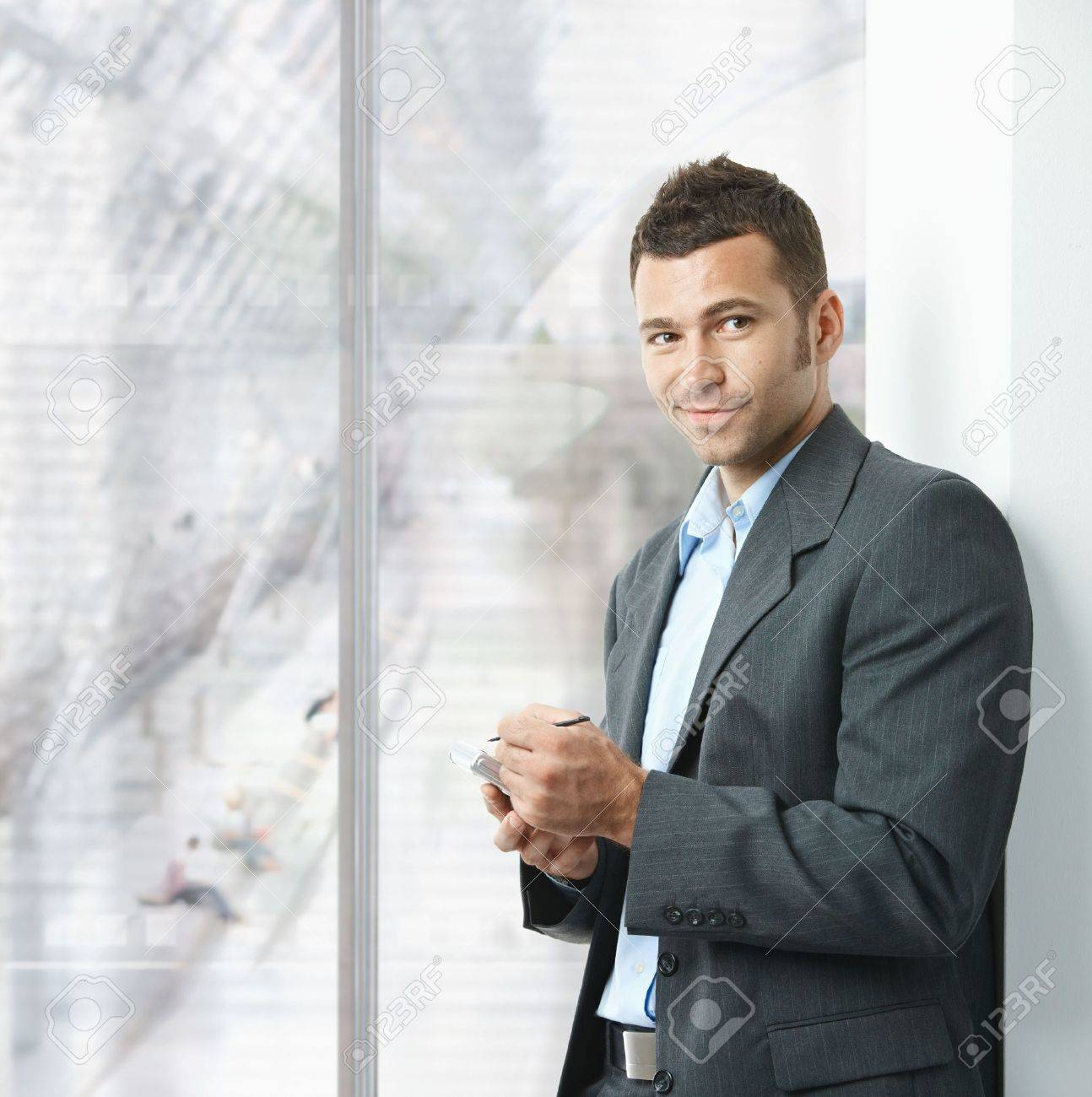 Young businessman standing in office lobby, using smartphone, smiling. Stock Photo - 5758822