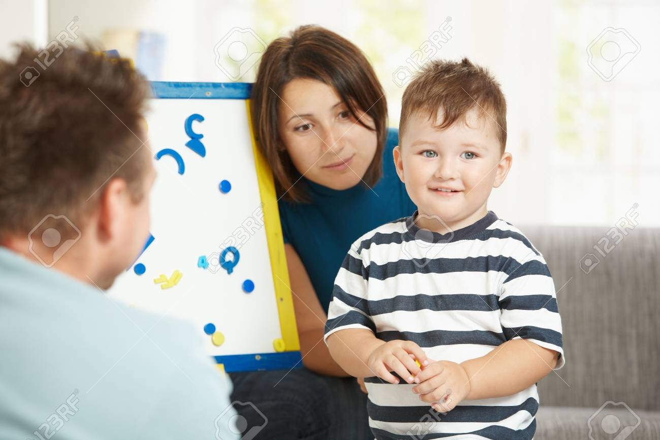 Father, mother and boy child playing together with toy whiteboard, letters and numbers. Stock Photo - 5766942