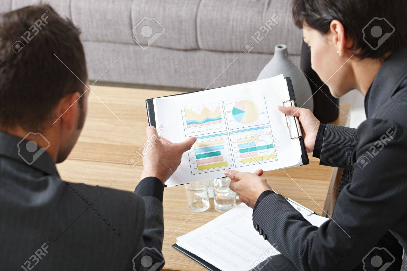 Business meeting at office. Youing businsspeople sitting on sofa, talking over financial charts. High angle view. Stock Photo - 5767075